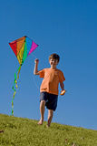 Boy Flying a Kite. Little Boy Flying a Kite Against a Blue Sky Stock Photo
