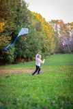Boy flying a kite in a clearing in the forest, Stock Photos
