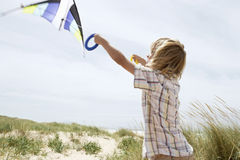 Boy Flying Kite On A Windy Beach Royalty Free Stock Photos