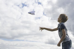 Boy flying a paper plane against blue sky Stock Image