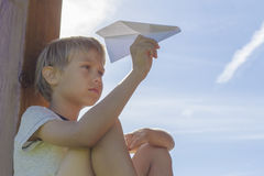 Boy flying a paper plane against blue sky. Summer day. Low angle view Stock Photos