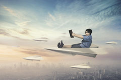 Boy flying with paper plane. Happy little boy flying with a paper plane while holding a book above a city Royalty Free Stock Photos