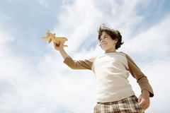 Boy Flying Toy Airplane Against Cloudy Sky Stock Image