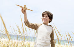 Boy Flying Toy Airplane Among Plants On Beach Stock Images
