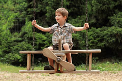 A boy flying on a wooden plane swing in park Stock Photography