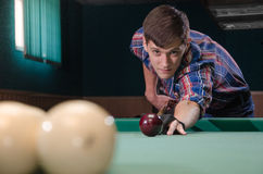 Boy in focus aiming for shot the billiard ball Stock Image
