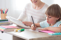 Boy focusing on homework. Boy focusing on his homework while sitting with mother at desk with notebook and colored pens stock photography