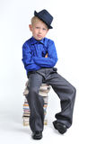 Boy with folded hands on the heap of books. Boy dressed with suit with folded hands, sitting on the heap of books Royalty Free Stock Photos