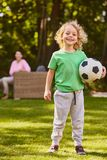 Boy with football ball. Little happy boy standing with a football ball royalty free stock image