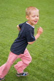 Boy on the football field. Boy running on the football field on a clear sunny day Royalty Free Stock Images
