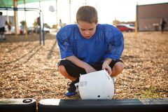 Boy with a football helmet. Boy squatting down getting ready to put on a footbal helmet royalty free stock image