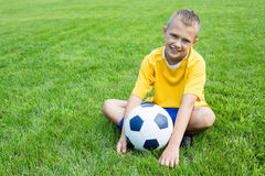 Boy football player with the ball is sitting on the football fie Royalty Free Stock Photos