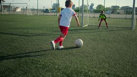 Boy football player is scoring goal. Soccer match in field stock video footage