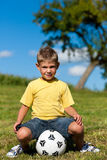 Boy with football sitting on a meadow. Happy little boy with football sitting on a meadow and is playing with it royalty free stock photos