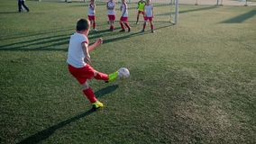 Boy footballer is kicking ball into goal through wall of players. Training on field stock video