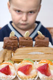 Boy forbidden to eat cakes Stock Photos