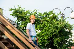 Boy in forest adventure park. Kid in orange helmet and white t shirt climbs on high rope trail. Climbing outdoor, amusement center stock photography