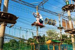Boy in forest adventure park. Kid in orange helmet and white t shirt climbs on high rope trail. Climbing outdoor stock images