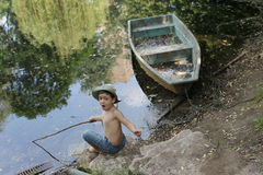 Boy in forest by lake Royalty Free Stock Photography
