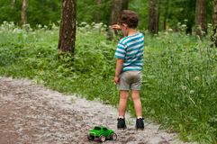 Boy on a forest trail. Three year old boy stands on the forest path. In one hand he holds a toy car on a string, with the other hand he plays with poplar fluff Stock Photo