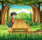 A boy in the forest with a wooden table and bench Stock Photo