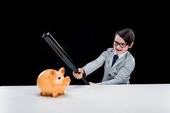 Boy in formal suit holding baseball bat hitting piggy bank Stock Image