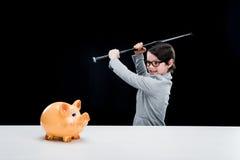 Boy in formal suit holding baseball bat hitting piggy bank Royalty Free Stock Photos