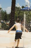 Boy in Fountain. Young Boy running through fountain Royalty Free Stock Image