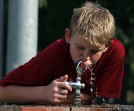 Boy At Fountain. Boy getting a much needed drink from a water fountain Royalty Free Stock Image