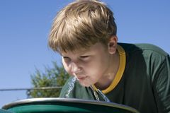Boy at Fountain. A child drinks from a water fountain royalty free stock images