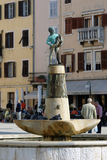 Boy fountain with a fish statue in Rovinj,Croatia Stock Photography