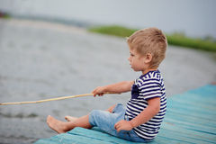 Boy of four on jetty by the sea Stock Photos