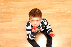 Boy four years old, strawberry taste. A little boy of four years wearing classic clothes and taste strawberries Stock Image