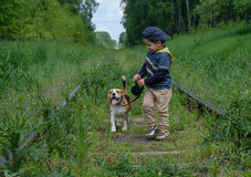 Boy, four years old walking with a Beagle. Boy, four years old walks on a leash with a Beagle dog on the sleepers of the railway Royalty Free Stock Photo