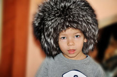 Boy in fox cap. Boy in the cap of the silver fox with an interesting face Royalty Free Stock Image