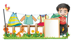 A boy with a frame in front of the hanging clothes Royalty Free Stock Image
