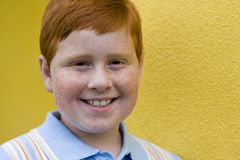 Boy (9-11) with freckles and ginger hair standing beside yellow wall, smiling, close-up, portrait Royalty Free Stock Images