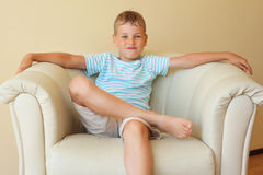 Boy freely sitting with magnificent easy chair. In cosy room royalty free stock image