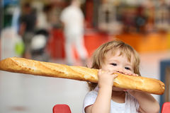 Boy with french bread. Closeup portrait of beautiful pretty cute hazel-eyed kid with shoulder-length blond wavy hair holding and biting French bread riding red royalty free stock image