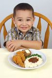 Boy and fried chicken. Boy ready to eat a dinner of fried chicken, mashed potatoes with gravy, green beans, and a whole wheat roll with butter royalty free stock photo