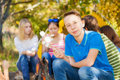 Boy and friends hold marshmallow sitting near tent Stock Photos
