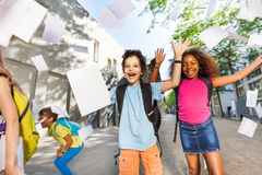 Boy with friends joy screaming throwing papers up. Happy very exited boy throwing papers in the air with friends near the school door Stock Photos