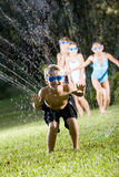 Boy with friends splashing in lawn sprinkler Royalty Free Stock Photo