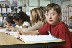 Boy With Friends Studying In Classroom Stock Photography