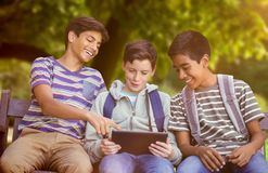 Composite image of boy with friends using digital tablet on bench Royalty Free Stock Images