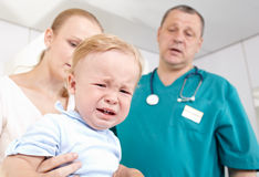 Boy is frightened and crying in a medical study. A 1,5 year-old boy is frightened and crying in a medical study. The doctor and the babys mother are at a loss Stock Photos