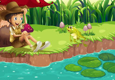 A boy and a frog at the riverbank Stock Photography