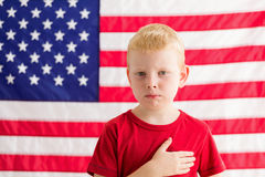 Boy in front of American flag with hand over heart Royalty Free Stock Image