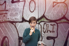 Boy in front of a big graffiti is eating his ice cream Royalty Free Stock Image
