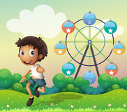 A boy in front of a ferris wheel Stock Photography